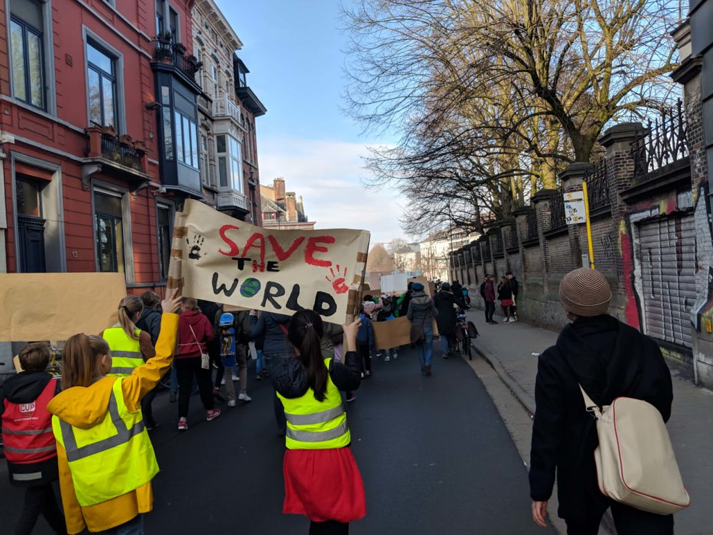 """Climate marchers in Ghent with a banner that reads """"save the world"""""""